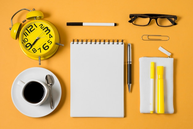 Notatnik na płasko i filiżanka kawy
