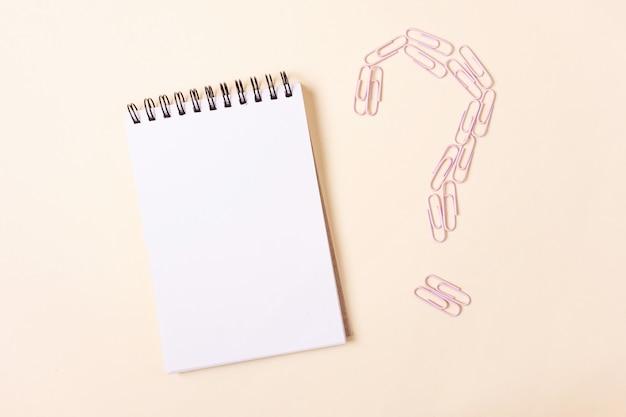 Notatnik na spiralnych i różowych spinaczach w kształcie znaku zapytania na beżowym tle