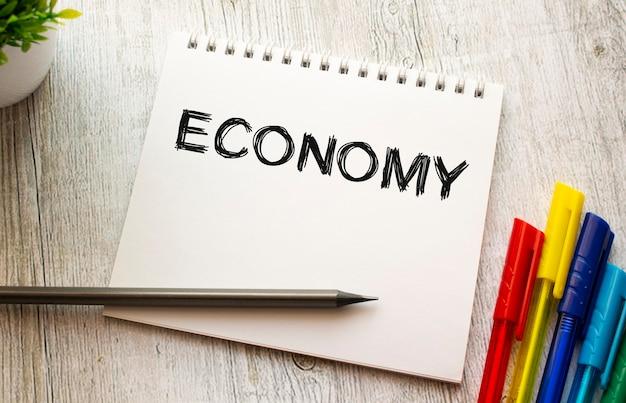 Notatnik na sprężynie z napisem gospodarka na białej prześcieradle leży na drewnianym stole z kolorowymi długopisami. pomysł na biznes.