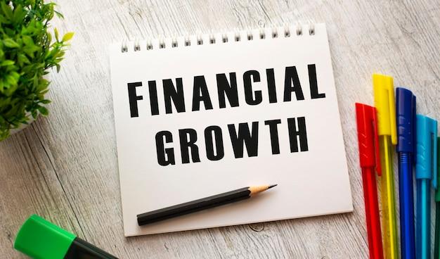Notatnik na sprężynie z napisem wzrost finansowy na białej prześcieradle leży na drewnianym stole z kolorowymi długopisami. pomysł na biznes.