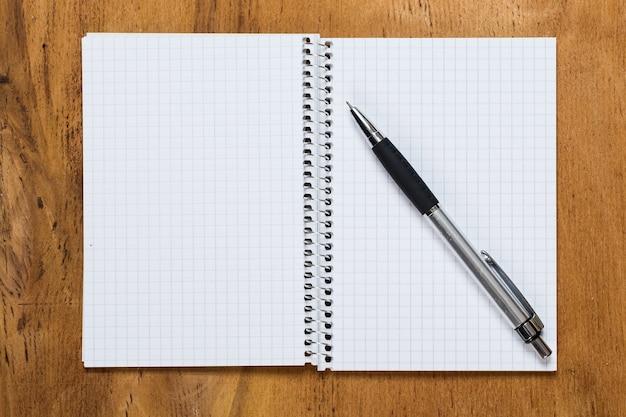 Notatnik na stole z długopisem