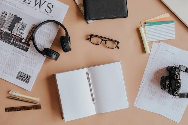 Notatnik na stole ze słuchawkami i aparatem