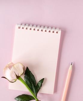 Notatnik na twój tekst na jasnoróżowej powierzchni z różowymi różami