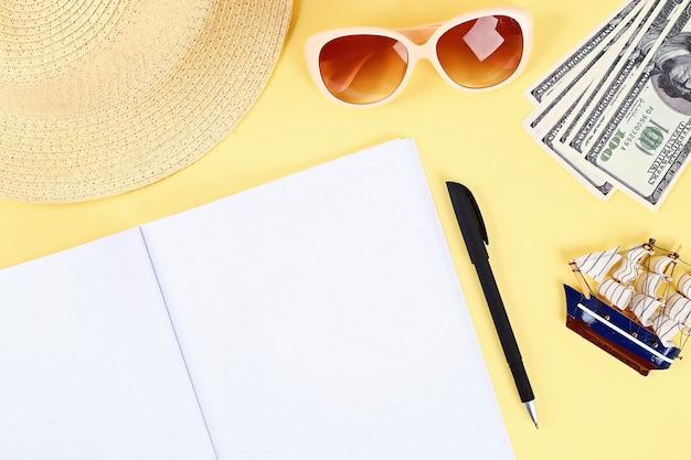 Notatnik na żółtym tle. koncepcja lato. przygotowanie do wakacji.