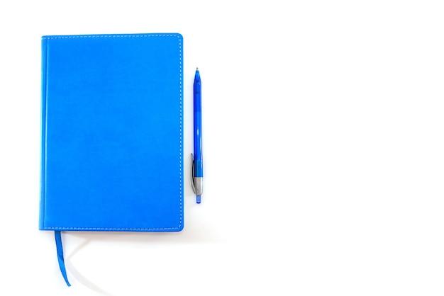 Notatnik niebieski i niebieski długopis na białym tle. skopiuj miejsce.