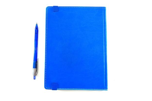 Notatnik niebieski i niebieski długopis na białym tle. zbliżenie.