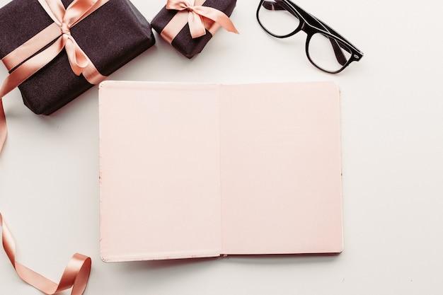 Notatnik, okulary i pudełko na białym tle.