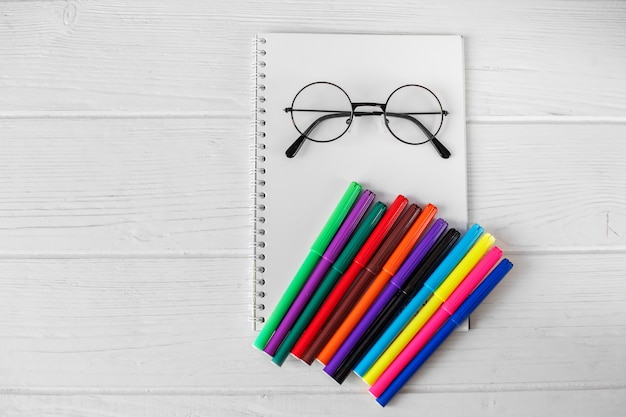 Notatnik, okulary i wiele kolorowych markerów.