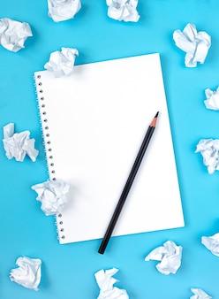 Notatnik, ołówek i kulki zmięty papier na niebieskim tle. koncepcja znalezienia pomysłu. skopiuj miejsce