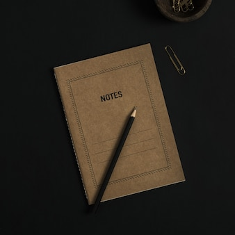 Notatnik, ołówek, klipsy w drewnianej misce na czarno