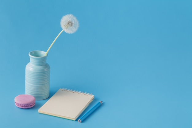 Notatnik, ołówek, mniszek lekarski na niebieskim tle biurko