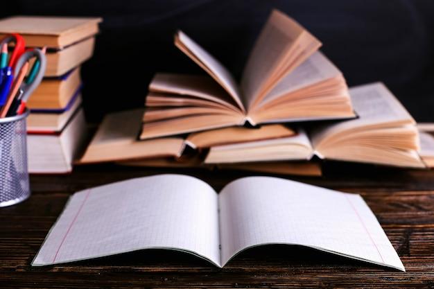 Notatnik, otwarte książki i przybory szkolne na ciemnym drewnianym stole na tle tablicy kredowej