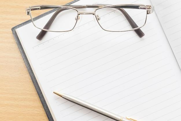 Notatnik otwarty pustą stronę i okulary