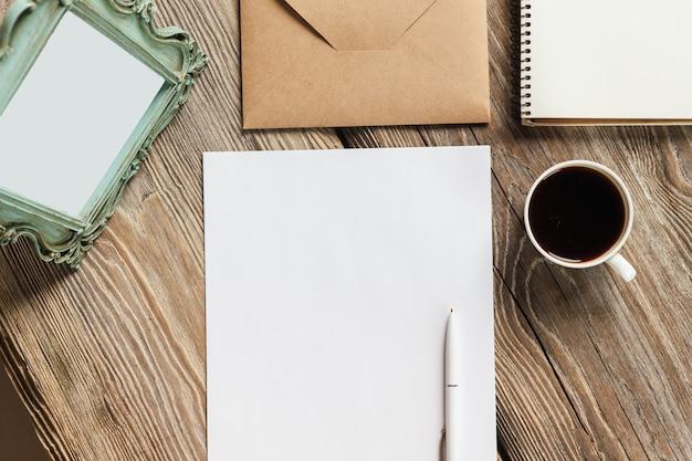 Notatnik, papier, filiżanka kawy i koperta z starą starą ramką na zdjęcia