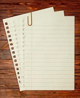 Notatnik papierowy. teksturowane na białym tle na tle drewna.