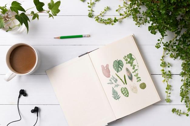 Notatnik płasko leżał w roślinach z ręcznie rysowanymi ilustracjami