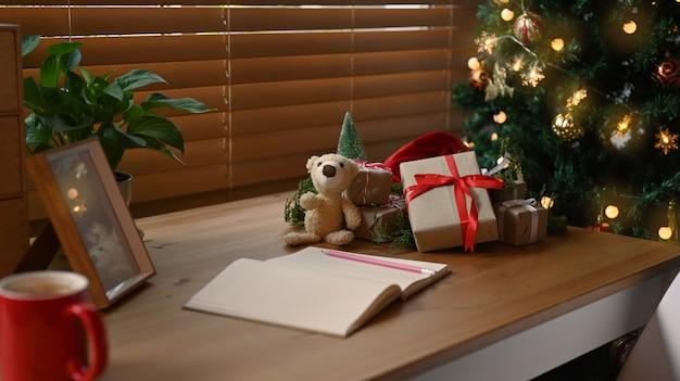 Notatnik, pudełka na prezenty i misia na drewnianym stole w pobliżu choinki w salonie.