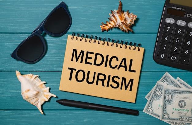 Notatnik rzemieślniczy z napisem turystyka medyczna, okulary, pieniądze, kalkulator i muszelki