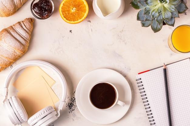 Notatnik, słuchawki, rogaliki i kawa na białym stole.