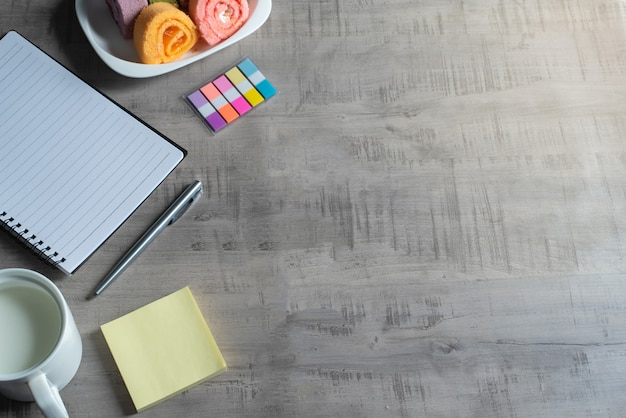 Notatnik, smartfon, dżem roll, szklanka mleka, długopis na drewnianej, papierowej notatce biznes, koncepcja edukacji i projekt