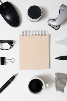 Notatnik spirali otoczony przez materiały biurowe; filiżanka kawy i okulary na białym tle na białym tle