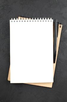 Notatnik spiralny z widokiem z góry czarny długopis na czarnym stole