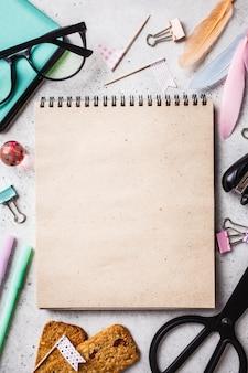 Notatnik, szkła, pióra i materiały przedmioty na szarym tle, odgórny widok.