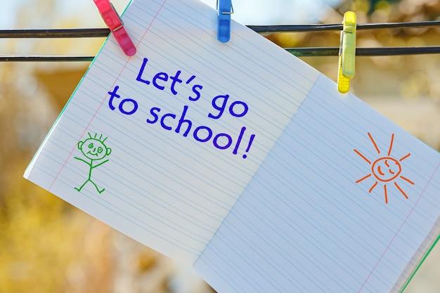 Notatnik szkolny z napisem - chodźmy do szkoły, wiszący na spinaczach do bielizny.