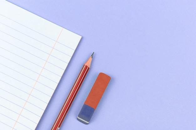 Notatnik szkolny z ołówkiem i gumką w tle szkolnego składu na fioletowym stole biurowym