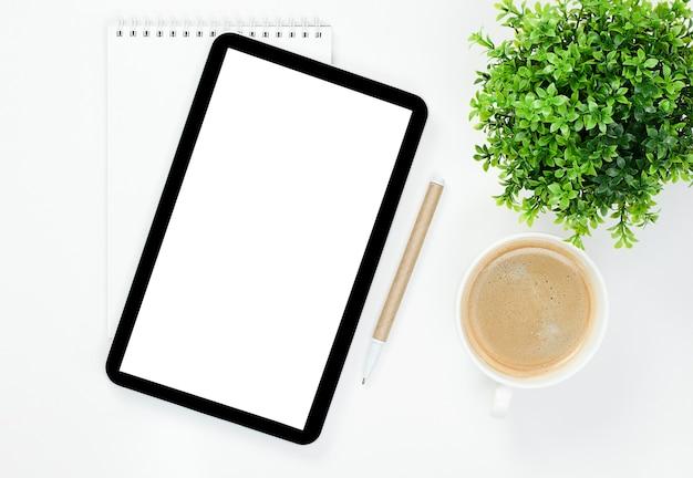 Notatnik, tablet cyfrowy, kawa, długopis i roślina na pulpicie.