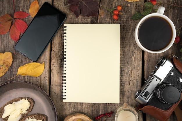Notatnik, talerz z kanapkami, filiżanka kawy, aparat fotograficzny, jesienne liście i jagody na naturalnym drewnianym tle.