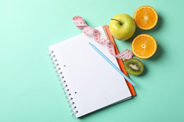 Notatnik, taśma miernicza, długopis i wegetariańskie jedzenie. utrata masy ciała