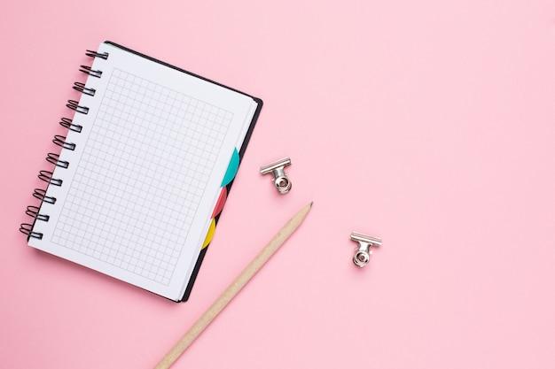 Notatnik w klatce z ołówkiem na różowym tle
