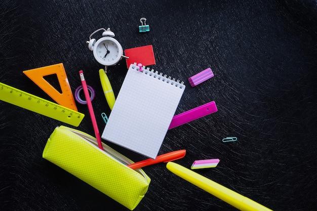 Notatnik w kratkę, budzik i różnokolorowe artykuły papiernicze wypadające z jasnożółtego piórnika na czarnym tle z teksturą.