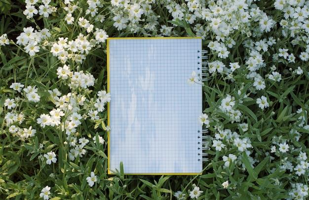 Notatnik w kratkę leży na kwiatach