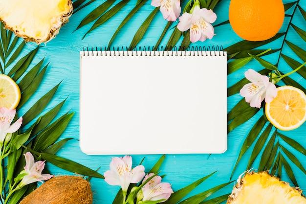 Notatnik wśród liści roślin i owoców w pobliżu kwiatów