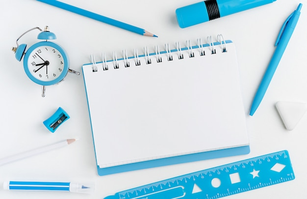 Notatnik z białym puste i papeterii na białym pulpicie. koncepcja edukacji. makieta, bezpośrednio powyżej.