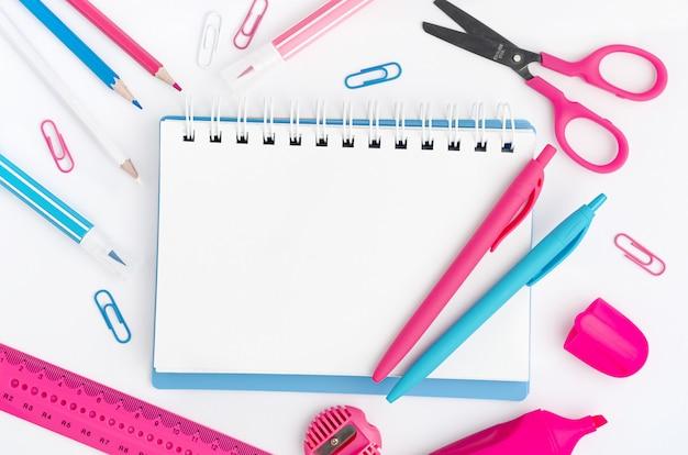Notatnik z białym pustym miejscem z kolorowymi artykułami na białym pulpicie. koncepcja edukacji. makieta, bezpośrednio powyżej.