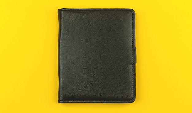 Notatnik z czarnej skóry na kolorowym żółtym stole biurowym, koncepcja dziennika biznesowego, makieta i miejsce na tekst, zdjęcie z widokiem z góry