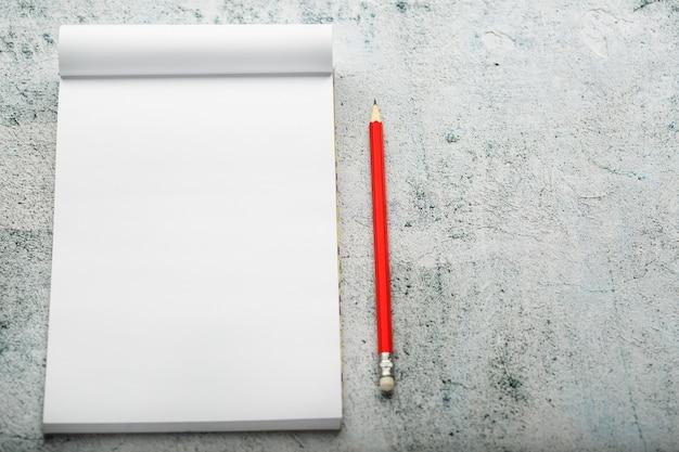 Notatnik z czerwonym ołówkiem na białej tynkującej ścianie