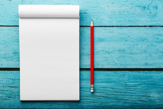 Notatnik z czerwonym ołówkiem na błękitnym drewnianym stołowym tle dla edukaci, pisze celach i czynach