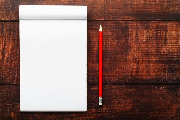 Notatnik z czerwonym ołówkiem na brown drewnianym stołowym tle dla edukaci, pisze celach i czynach