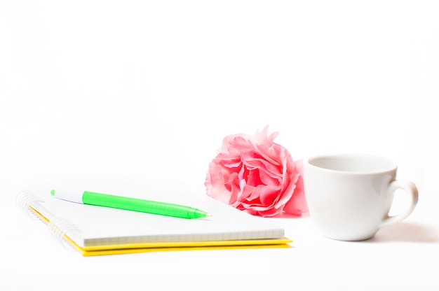 Notatnik z czerwonymi kwiatami i filiżanką na białym tle