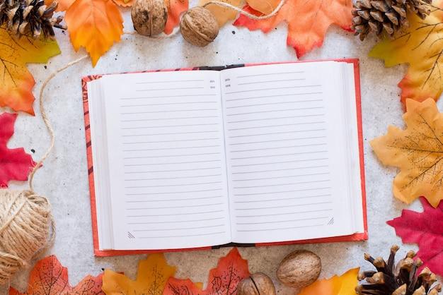 Notatnik z czystymi prześcieradłami na szarym tle z jasnymi jesiennymi liśćmi. koncepcja jesiennego nastroju. płaski układanie, widok z góry, kopia przestrzeń