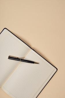 Notatnik z długopisem akcesoria biurowe na beżowym tle.