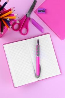 Notatnik z długopisem i innymi przyborami szkolnymi na różowym tle.