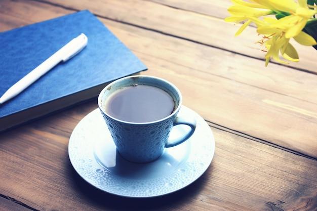 Notatnik z długopisem, kawą i kwiatkiem na drewnianym stole