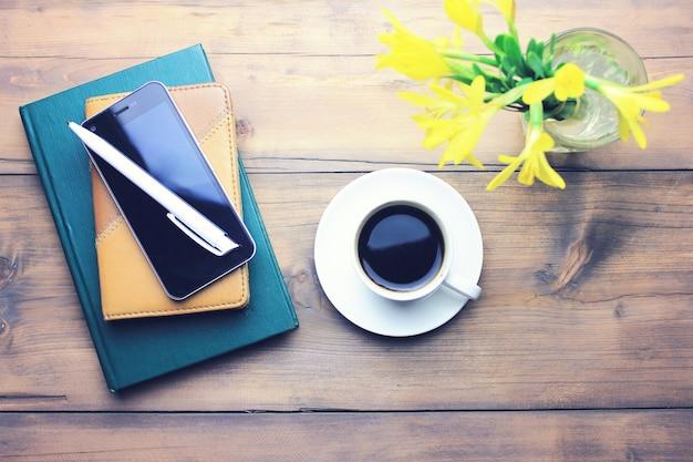 Notatnik z długopisem, kawą, telefonem i kwiatem na drewnianym stole