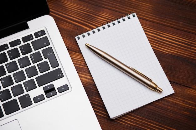 Notatnik z długopisem leży obok laptopa na drewnianym stole.