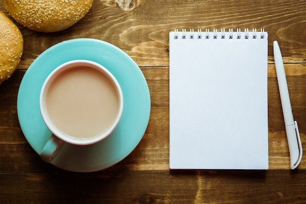 Notatnik z długopisem na stole obok kakao